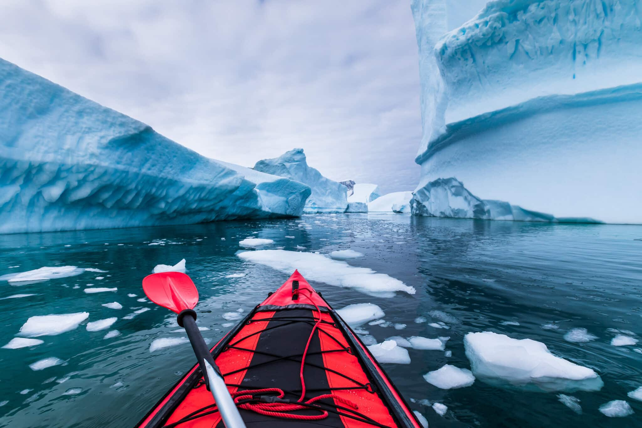 Kayaking in Antarctica between icebergs with inflatable kayak, extreme adventure in Antarctic Peninsula , beautiful pristine landscape, sea water paddling activity